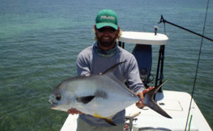 Flats fishing captain with a Permit fish
