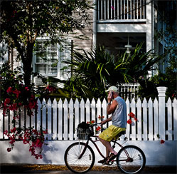 Man riding bicycle in Key West with wooden house and fence in view