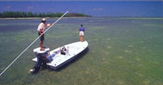 Flats fishing guide pushes skiff with pole while angler casts
