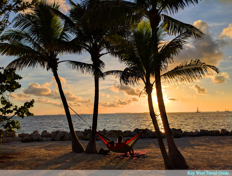 Two visitors to Fort Zachary Taylor State Park enjoy the sunset while swinging in a hammock
