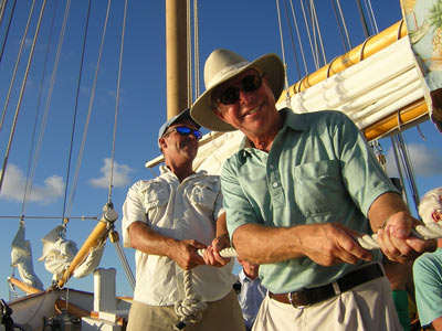 Raising the main sail aboard a traditional sailing schooner.