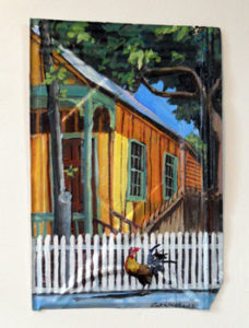 Rick Worth painting on metal roofing shingle of a rooster and wooden house