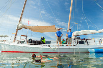 Snorkelers swimming away from the anchored schooner in the calm seas of the Key West backcountry islands