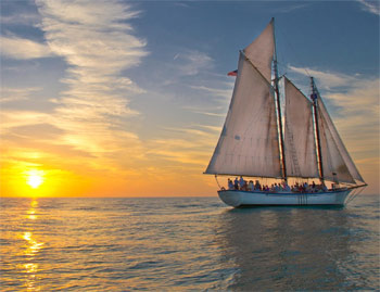 Tall ship schooner with full sails up just before sunset in Key West